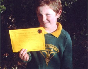 boy holding certificate of merit